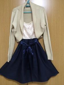 クリーム色とネイビー色のバイカラードレスの上にベージュのニットをコーディネート